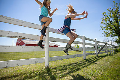 Playful sisters jumping off fence at sunny rural farm - p1192m2009244 by Hero Images