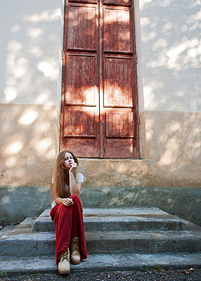 Girl in red skirt on the steps of the old building - p1412m1466349 by Svetlana Shemeleva