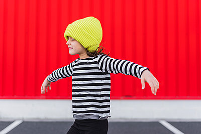 Little girl wearing striped shirt and yellow cap balancing - p300m2102730 by Eloisa Ramos