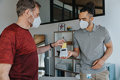 Physiotherapist in protective face mask holding credit card reader while patient paying in medical practice - p300m2275979 by Mareen Fischinger