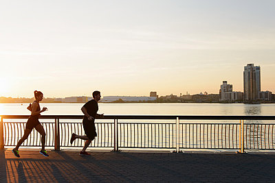 Jogging couple running on riverside early morning - p924m836493f by Matt Dutile