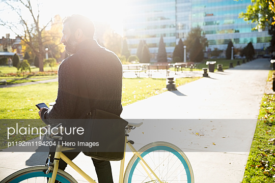 Businessman commuting with bicycle texting with cell phone in sunny urban park - p1192m1194204 by Hero Images