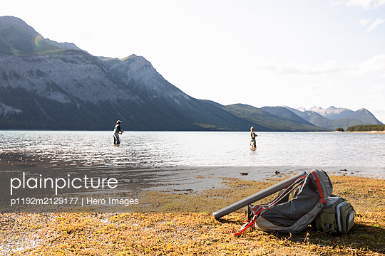 Mother and son fly fishing in sunny, scenic lake - p1192m2129177 by Hero Images