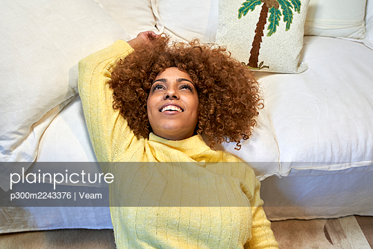 Smiling woman leaning on sofa after work in living room - p300m2243376 by Veam