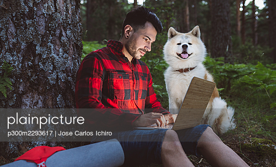 Mid adult man using laptop while sitting with dog at forest - p300m2293617 by Jose Carlos Ichiro