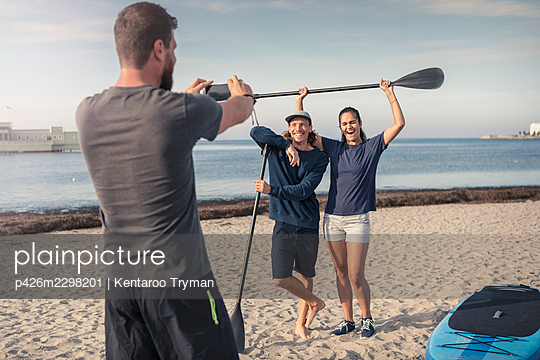 Man photographing happy male and female friends at beach during summer vacation - p426m2298201 by Kentaroo Tryman