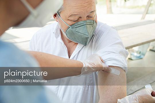 Austria, Vienna, Close-up of nurse applying adhesive bandage on patients arm - p924m2300650 by Manuela
