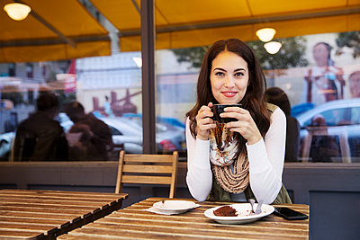 Portrait of woman holding coffee cup while sitting at sidewalk cafe - p1166m1204401 by Cavan Images