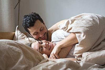 Junges Paar liegt nebeneinander unter einer Decke und lacht  - p1301m1424740 von Delia Baum