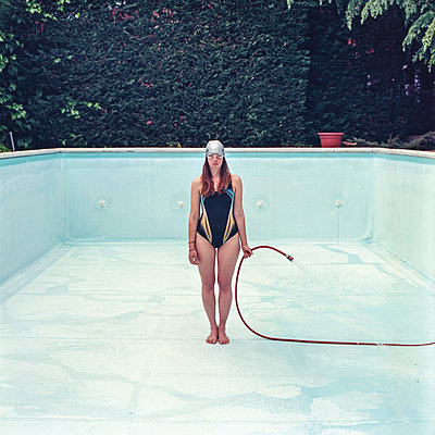 Woman holding garden hose in pool - p1462m2027440 by Massimo Giovannini