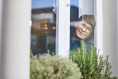 Smiling woman at home looking out of window - p300m2188883 by Maya Claussen