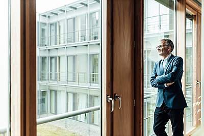 Smiling male entrepreneur with arms crossed looking through glass in corridor - p300m2266291 by Gustafsson