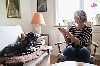Senior woman photographing dog through smart phone at home - p426m1114760f by Maskot