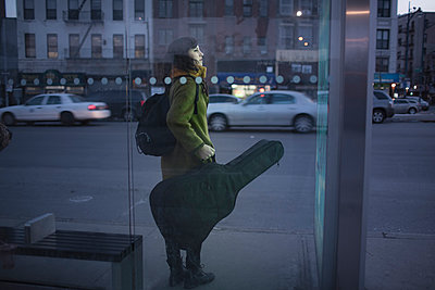 Young woman carrying guitar case - p429m897074 by Chad Springer