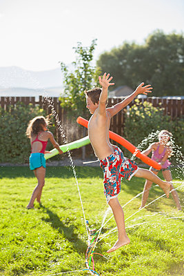 Caucasian children playing in the sprinkler - p555m1479003 by Mike Kemp