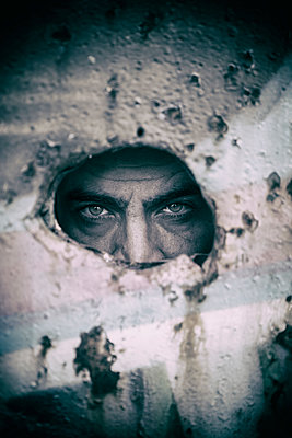 Creepy man looking through a hole in the wall  - p794m1589029 by Mohamad Itani
