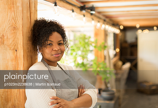 Portrait confident female shop owner in plant nursery - p1023m2238638 by Martin Barraud