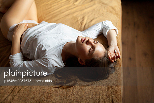 Young woman lying on be - p1646m2237678 by Slava Chistyakov