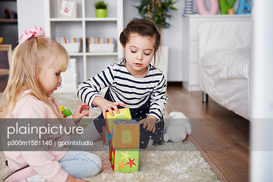 Two little girls playing with toy blocks on carpet at home - p300m1581140 by gpointstudio