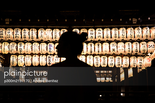 Japan,KyotoPrefecture,KyotoCity, Silhouette of woman admiring rows of lanterns glowing in Japanese temple at night - p300m2197170 by Andrés Benitez