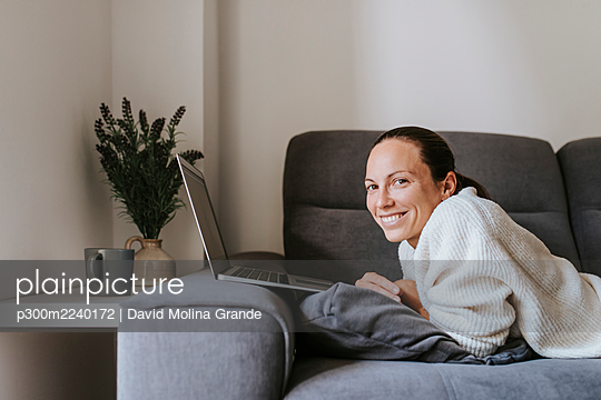 Smiling woman lying with laptop on sofa in living room - p300m2240172 by David Molina Grande