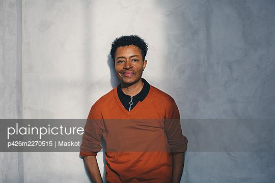 Portrait of smiling male entrepreneur against gray wall - p426m2270515 by Maskot