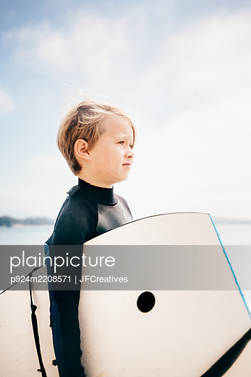 Portrait of young boy wearing wet suit, carrying surfboard into ocean, Santa Barbara, California, USA. - p924m2208571 by JFCreatives