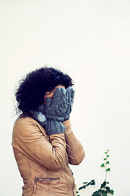 Woman covering face with hands - p879m1503532 by nico