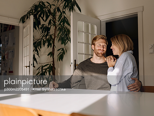 Happy affectionate couple sitting at table at home - p300m2205491 by Kniel Synnatzschke
