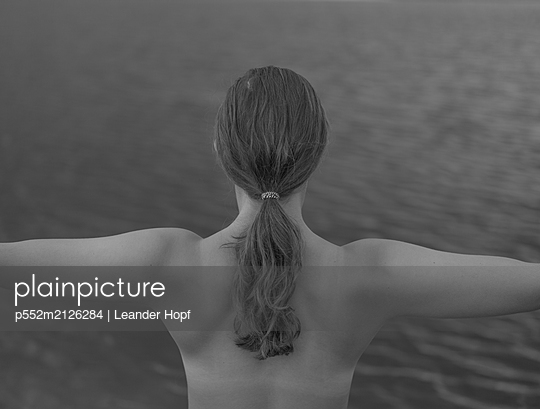 Rear view of young woman with arms outstretched on the waterfront - p552m2126284 by Leander Hopf