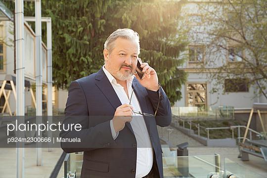 Austria, Vienna, Businessman talking on smart phone in city - p924m2300666 by Manuela