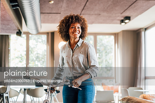 Italy, Smiling businesswoman with bicycle in creative studio - p924m2300763 by Eugenio Marongiu