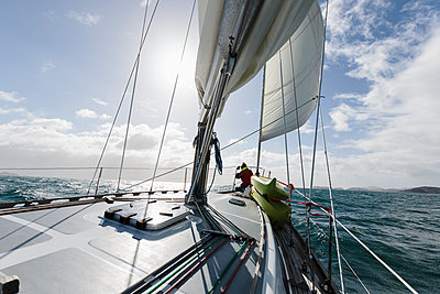 Woman at bow of sailboat on sunny ocean, Vava'u, Tonga, Pacific Ocean - p1023m2024434 by Martin Barraud