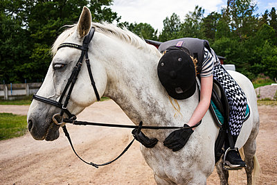 A young girl hugging her horse - p352m1523399 by Mattias Ahlm