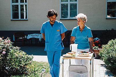 Male nurse walking with senior woman pushing food cart against nursing home - p426m2074253 by Maskot