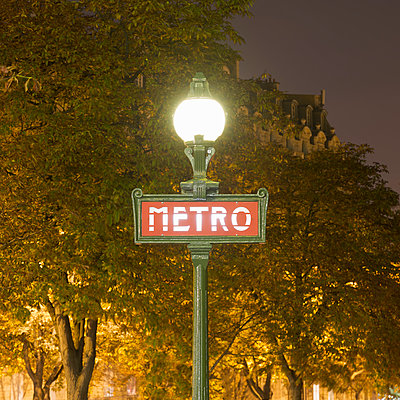 View of street lamp and metro sign at night, Paris, France - p429m1014617 by Alex Holland