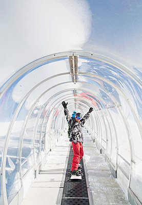 Portrait of snowboarder in ski run tunnel, on moving walkway - p429m1519425 by Guido Cavallini