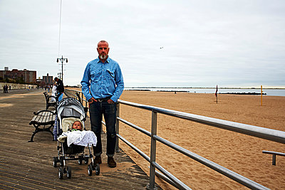 Man with baby boy in push chair at seaside - p429m802501 by Cultura