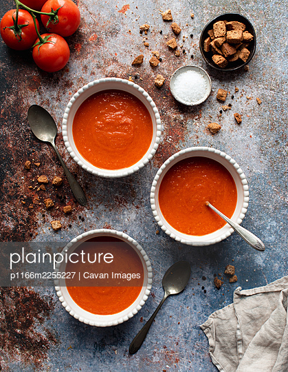 Overhead flat lay of bowls of tomato soup on gray stone background. - p1166m2255227 by Cavan Images