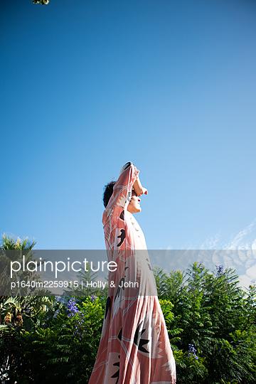 Woman under blue sky - p1640m2259915 by Holly & John