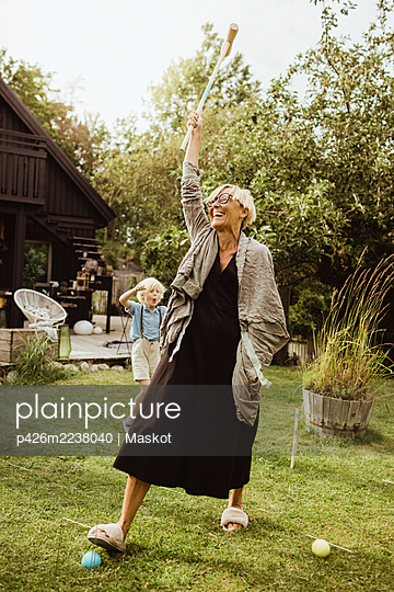 Cheerful grandmother playing polo with grandson in back yard at evening - p426m2238040 by Maskot