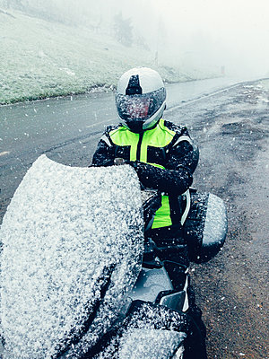 Snow covered motorcyclist sitting on motorcycle - p1053m2015592 by Joern Rynio