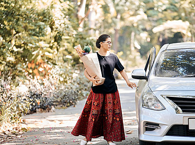 A woman hold a paper bag of dry flower and back to car after shopping - p1166m2234759 by Cavan Images