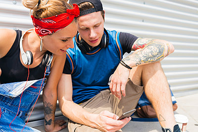 Young couple sitting on ground looking at smartphone - p300m2012530 by Francesco Morandini