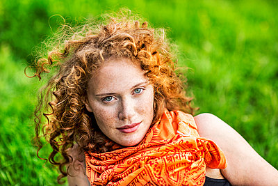 Portrait of freckled young woman with curly red hair wearing orange scarf - p300m2029202 by Jo Kirchherr