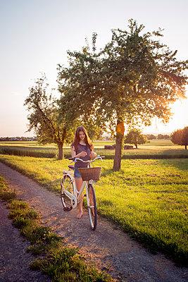 Teenage girl standing next to bike on dirt road at sunset - p300m2132270 by Larissa Veronesi