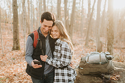 Young couple taking smart phone selfie during autumn hike - p300m2241437 by Sara Monika