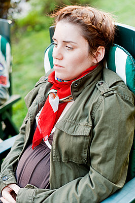 Woman sitting on chair outdoors - p312m1551969 by Johner Images