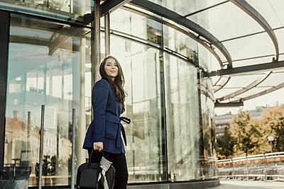 Businesswoman walking, office building in background - p312m2262579 by Plattform