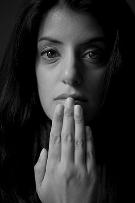 Dark-haired woman with hand to chin - p552m2275776 by Leander Hopf